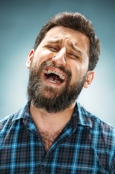 青いシャツを着て泣いている男