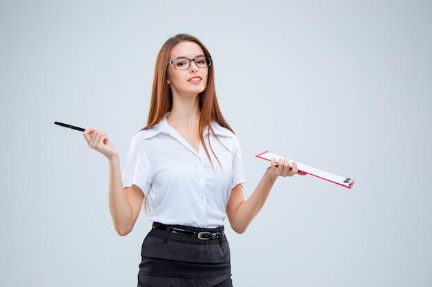 Улыбающаяся молодая деловая женщина с ручкой и планшетом для заметок на сером фоне