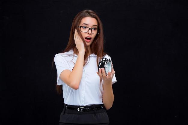 黒の背景に目覚まし時計を持つ若いビジネス女性