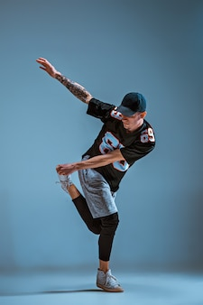 若い男は壁の背景にブレイクダンス。