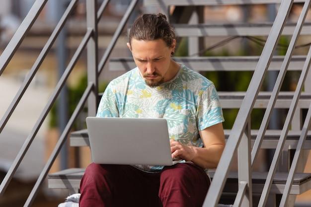 コンピューターの画面上で探しているラップトップで屋外で働くビジネスマン