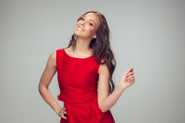 Красивая молодая женщина позирует с красным платьем