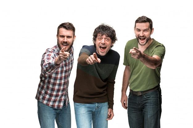 Трое мужчин улыбаются, глядя и указывая на камеру