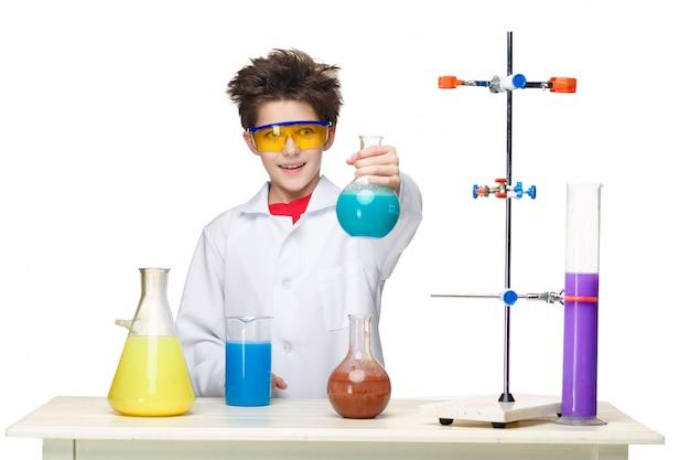 Маленький мальчик как химик делает эксперимент с химической жидкостью в лаборатории