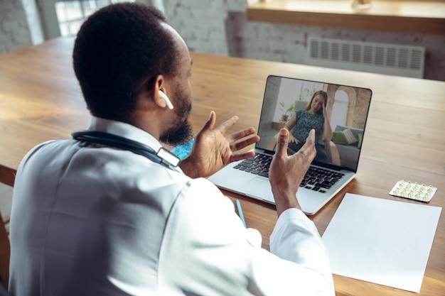 ノートパソコンでオンラインで患者に助言する医師