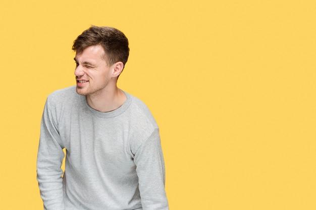 疲れたビジネスマンや痛みと黄色のスタジオの背景に深刻な若い男