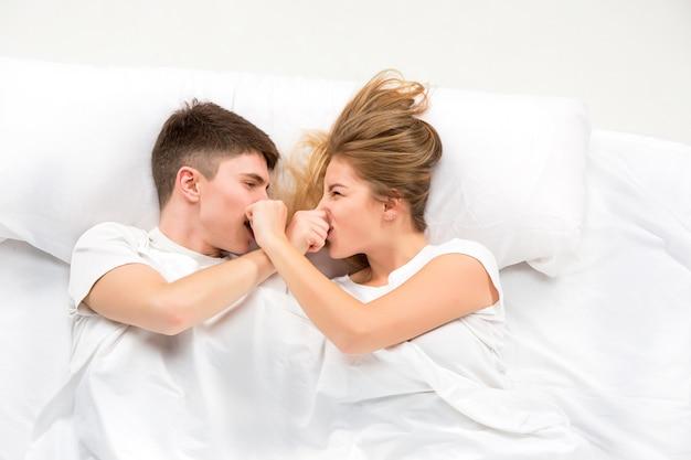 ベッドで横になっている若い素敵なカップル