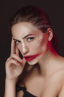 色の顔が描かれたファッションモデルの女の子。カラフルな抽象的なメイクと美しい女性の美容ファッションアートの肖像画。