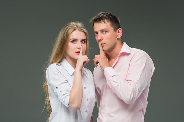 Портрет молодой пары, стоя на сером фоне