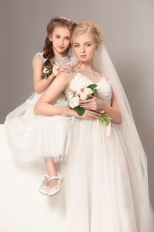Маленькие красивые девушки с цветами, одетые в свадебные платья