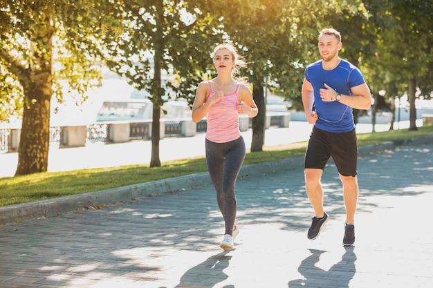 スポーティな女性と男の日の出の光の中で公園でジョギング