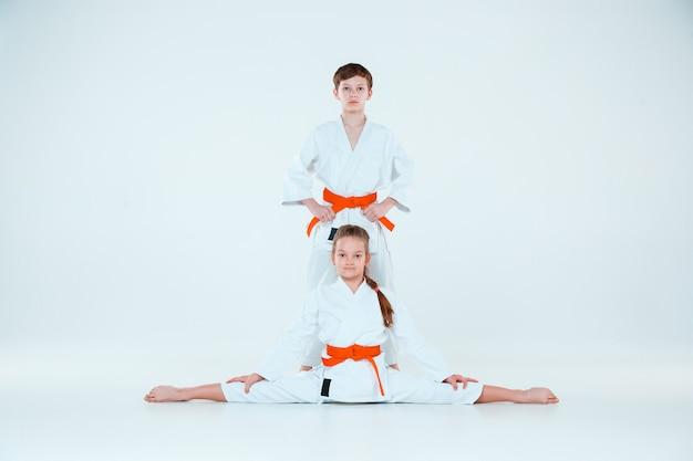 武道学校の合気道訓練でポーズをとる男の子と女の子。健康的なライフスタイルとスポーツのコンセプト