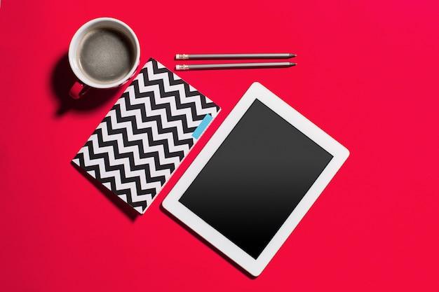 スマートフォンと一杯のコーヒーとモダンな赤いオフィスデスクテーブル。