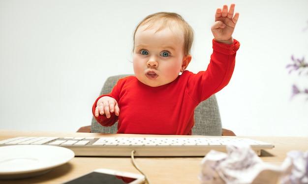 Счастливый малыш ребёнка сидя с изолированной клавиатурой компьютера
