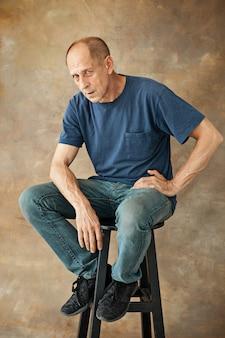 Взволнованный зрелый человек сидит в студии