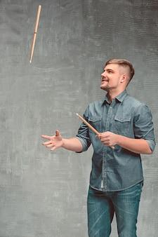 Мужчина держит две барабанные палочки над серым пространством