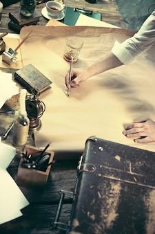 Архитектор работает над чертежным столом в офисе