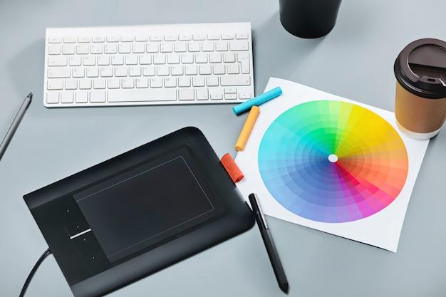 ラップトップ付きグレーの机、白紙のメモ帳、フラワーポット、スタイラス、レタッチ用タブレット