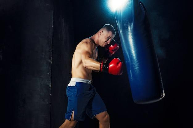 Мужской боксер бокс в боксерской грушей с драматическим острым освещением