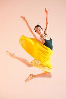 若い、信じられないほど美しいバレリーナがスタジオで踊っています。