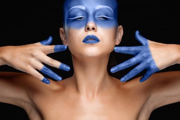 Портрет женщины, которая позирует покрыта синей краской