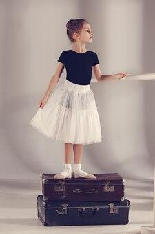 スタジオに立っているバレリーナダンサーとしての小さな女の子