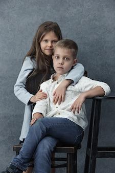 Маленькая девочка и мальчик на сером