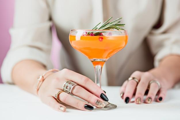 バラのエキゾチックなカクテルとフルーツと女性の手