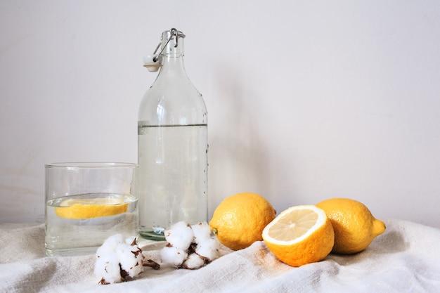 Вкусный прохладный напиток с лимоном на белой хлопчатобумажной ткани