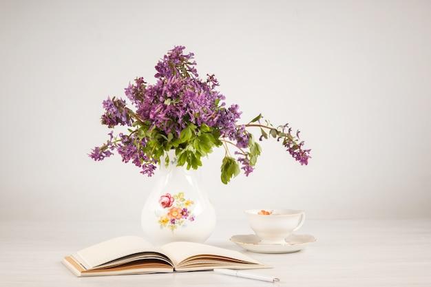 レモンとテーブルの上のライラックプリムローズの花束とお茶