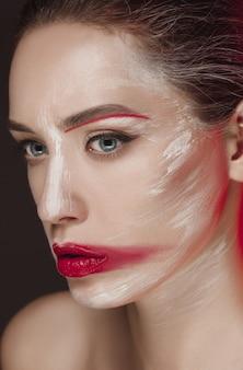 Мода модель девушка с цветным лицом окрашены.