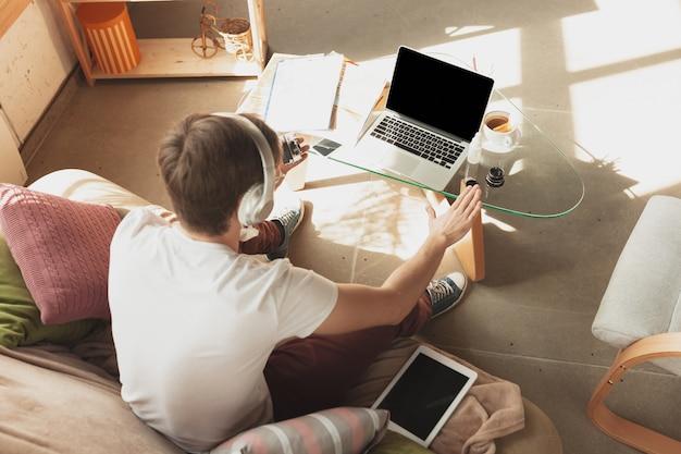 Молодой человек учится на дому во время онлайн-курсов