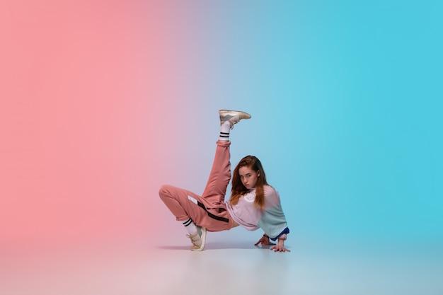 ネオンの光の中でダンスホールでグラデーションの背景にスタイリッシュな服でヒップホップを踊っている少女。