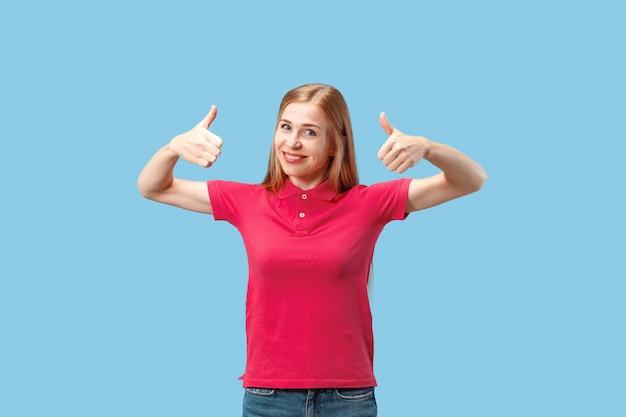 Счастливая бизнес-леди стоя и усмехаясь против голубой стены