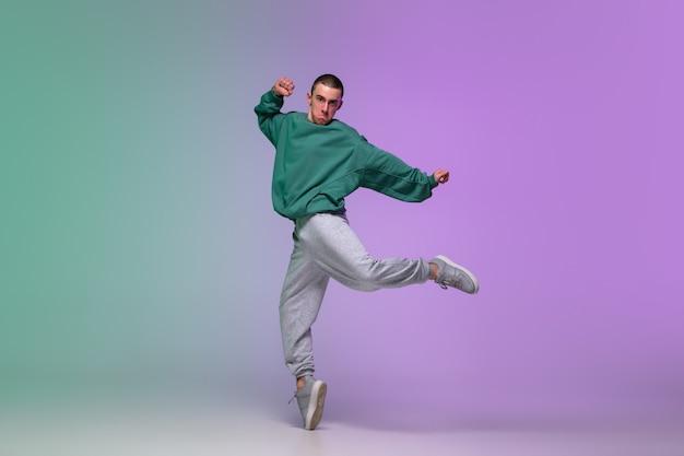 ネオンの光の中でダンスホールでグラデーションの背景にスタイリッシュな服でヒップホップを踊っている少年。