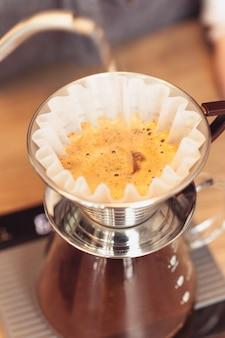 バリスタは、フィルターで挽いたコーヒーに水を注ぐ