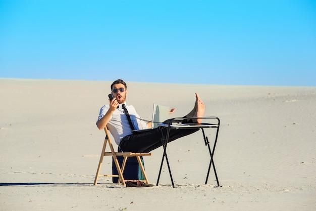 Бизнесмен, используя ноутбук в пустыне