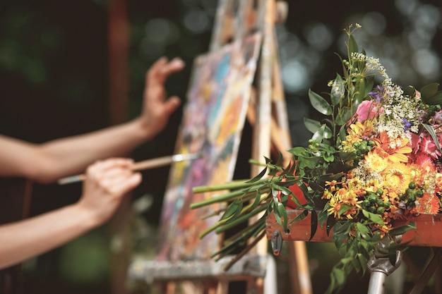 Рука художника крупным планом на фоне картины