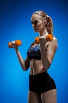 Спортивная женщина делает аэробные упражнения с красными гантелями