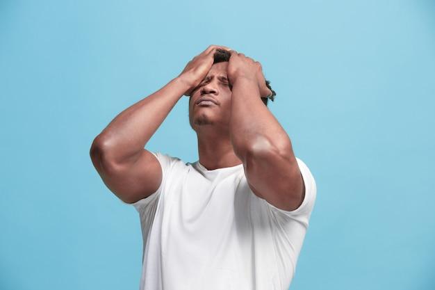 頭痛を持つアフリカ系アメリカ人の男。青い背景に分離されました。