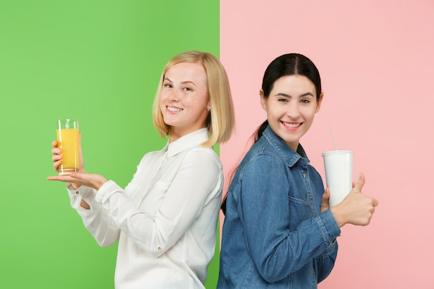 ダイエット。ダイエットのコンセプトです。健康食品。フルーツオレンジジュースと不快な炭酸の甘い飲み物の間で選択する美しい若い女性
