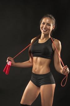 Мускулистые молодая женщина спортсмен со скакалкой на черном