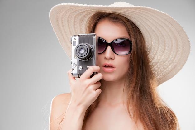 Девушка в широкополой шляпе и очках с ретро-камерой