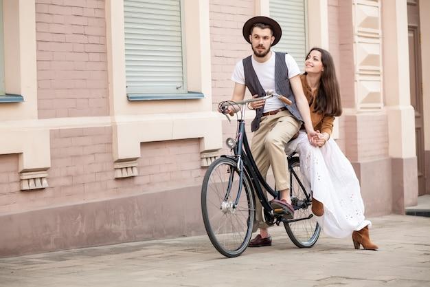 壁に自転車に座っている若いカップル
