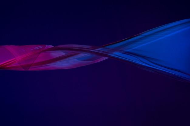 青の背景に区切られた滑らかでエレガントな透明な青い布。