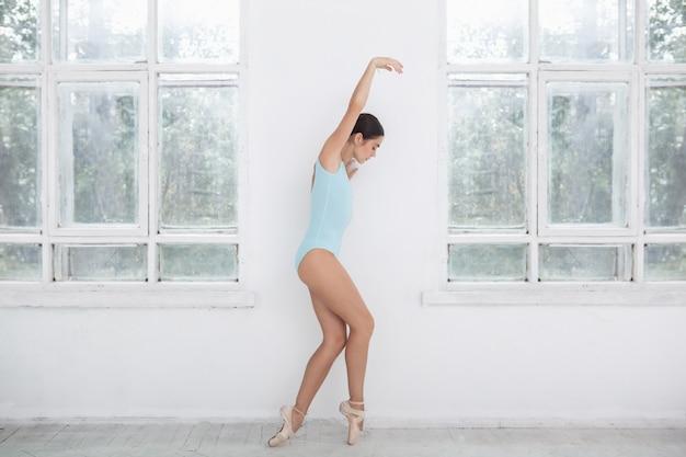 白でポーズ若い現代バレエダンサー