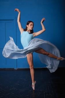 Молодая современная балерина позирует на синем