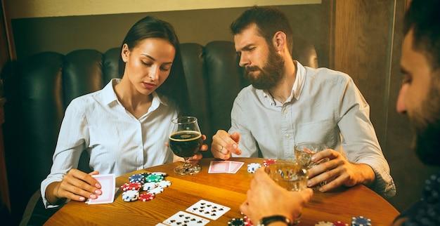 Фото взгляда со стороны друзей сидя на деревянном столе. друзья веселятся во время игры в настольную игру.