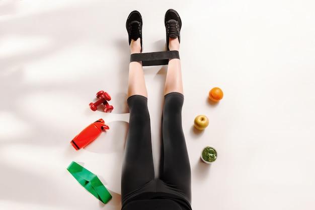 床に健康的な食品と運動の女の子