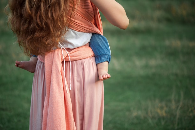 屋外に彼女の小さな幼児の息子を抱いて若い美しい母親